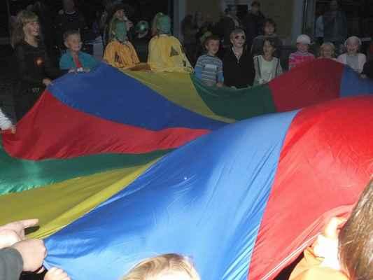 Oblíbená hra Padák. Dle barev se pod ním děti na povel schovávají nebo se na něm snaží udržet míč.